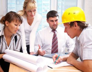 Contractor discussing plans with clients