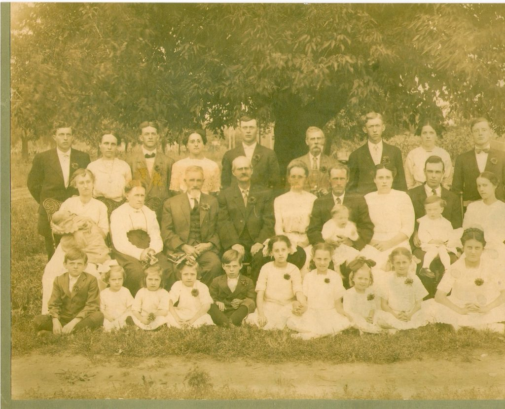 The gentleman 6th from the right with the beard is William Emmons (1st generation)  Second row man holding the baby is Joe (Pop) Emmons (2nd generation)  Baby on the lap is Alvin Emmons (he doesn't know it yet, but he will be the 3rd generation)